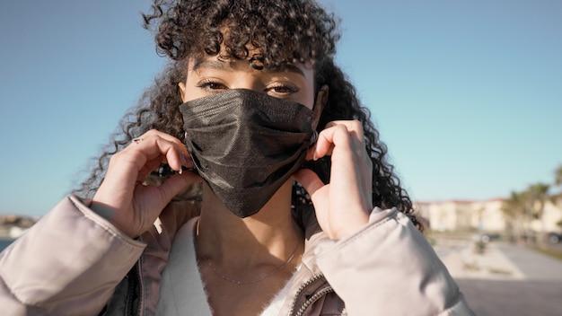 코로나 바이러스 감염을 피하기 위해 검은 마스크를 쓰고있는 동안 젊은 아프리카 계 미국인 여자의 초상화를 닫습니다.