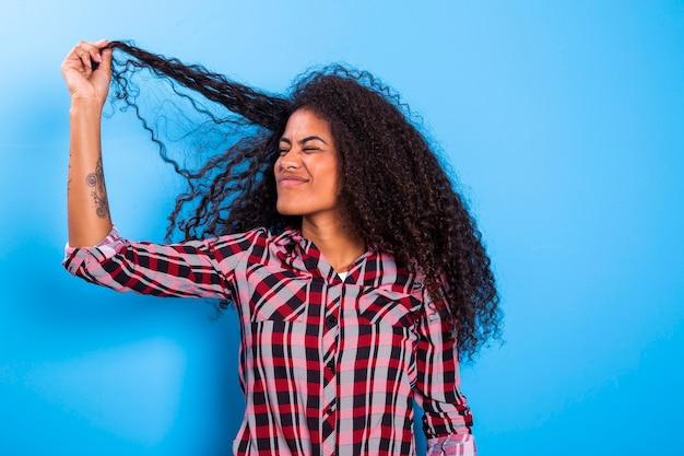 Крупным планом портрет молодой африканской женщины, тянет плохо вьющиеся волосы и выглядит обеспокоенным.
