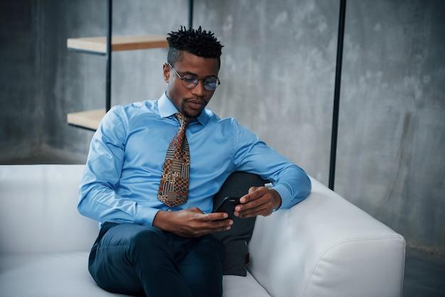 Крупным планом портрет молодого афро-американского парня в очках и классической одежде, сидя на диване