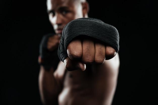 彼の拳を示す若いafroamericanボクサーのクローズアップの肖像画