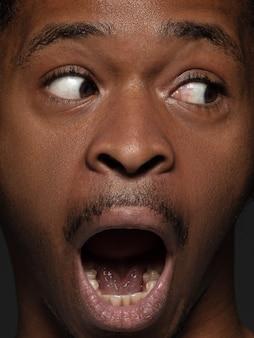Закройте вверх по портрету молодого и эмоционального афро-американского человека. детализированная фотосессия мужской модели с ухоженной кожей и ярким выражением лица. понятие о человеческих эмоциях. испуганный крик.