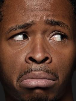Закройте вверх по портрету молодого и эмоционального афро-американского человека. детализированная фотосессия мужской модели с ухоженной кожей и выражением лица. понятие о человеческих эмоциях. расстроен, грустен, демотивирован.