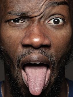 若くて感情的なアフリカ系アメリカ人の男の肖像画をクローズアップ。手入れの行き届いた肌と表情の男性モデルの非常に詳細な写真撮影。人間の感情の概念。舌を垂らして。