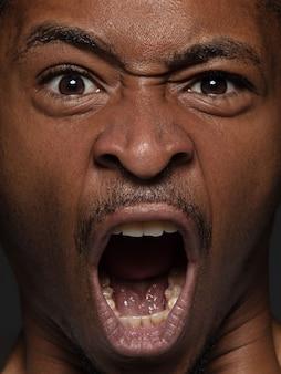 若くて感情的なアフリカ系アメリカ人の男の肖像画をクローズアップ。手入れの行き届いた肌と明るい表情の男性モデル。人間の感情の概念。怒っている叫び。