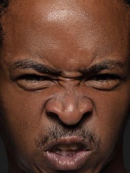 若くて感情的なアフリカ系アメリカ人の男の肖像画をクローズアップ。手入れの行き届いた肌と明るい表情の男性モデル。人間の感情の概念。怒っている。