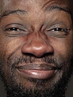 若くて感情的なアフリカ系アメリカ人の男の肖像画をクローズアップ。手入れの行き届いた肌と明るい表情の男性モデル。人間の感情の概念。幸せなしかめっ面。
