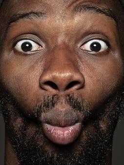 젊고 감정적 인 아프리카 계 미국인 남자의 초상화를 닫습니다. 잘 관리 된 피부와 밝은 표정을 가진 남성 모델. 인간 감정의 개념. 행복하게 찡그린 다.