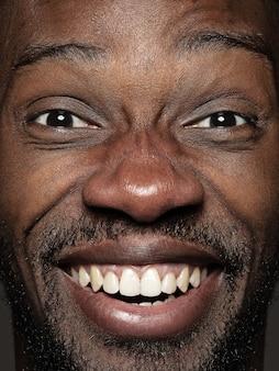 若くて感情的なアフリカ系アメリカ人の男の肖像画をクローズアップ。手入れの行き届いた肌と明るい表情の男性モデル。人間の感情の概念。幸せな笑顔。