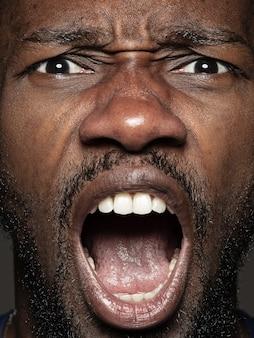 젊고 감정적 인 아프리카 계 미국인 남자의 초상화를 닫습니다. 잘 관리 된 피부와 밝은 표정을 가진 남성 모델. 인간 감정의 개념. 외침.
