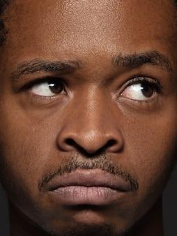 젊고 감정적 인 아프리카 계 미국인 남자의 초상화를 닫습니다. 잘 관리 된 피부와 밝은 표정을 가진 남성 모델. 인간 감정의 개념. 인정 있는.