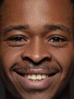 若くて感情的なアフリカ系アメリカ人の男の肖像画をクローズアップ。手入れの行き届いた肌と明るい表情の男性モデル。人間の感情の概念。