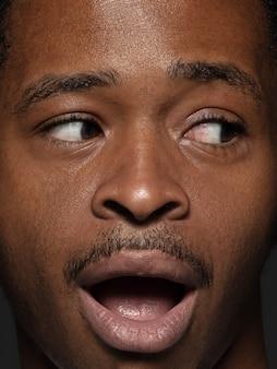 若くて感情的なアフリカ系アメリカ人の男の肖像画をクローズアップ。手入れの行き届いた肌と表情の男性モデル。人間の感情の概念。横を見ると、遊び心があります。