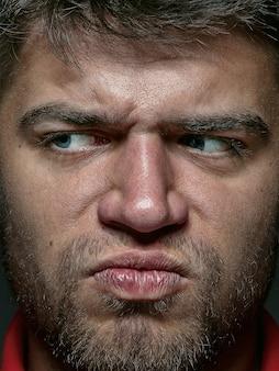 若くて感情的な白人男性の肖像画をクローズアップ。手入れの行き届いた肌と明るい表情の男性モデルの非常に詳細な写真撮影。人間の感情の概念。