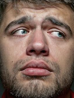 젊고 감정적 인 백인 남자의 초상화를 닫습니다. 잘 관리 된 피부와 밝은 표정으로 남성 모델의 매우 디테일 한 사진 촬영. 인간 감정의 개념. 슬프고 속상해 보입니다.