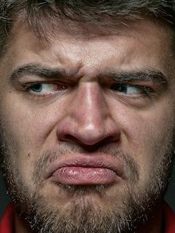 若くて感情的な白人男性の肖像画をクローズアップ。手入れの行き届いた肌と明るい表情の男性モデル。人間の感情の概念。怒っている。