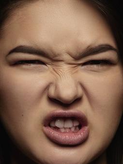 젊고 감정적 인 중국 여자의 초상화를 닫습니다. 깔끔한 피부와 밝은 표정으로 여성 모델의 세밀한 사진 촬영. 인간 감정의 개념. 화가 나고 무섭다.