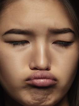 若くて感情的な中国人女性の肖像画をクローズアップ。手入れの行き届いた肌と明るい表情の女性モデルの非常に詳細な写真撮影。人間の感情の概念。悲しそうに見え、気分を害します。