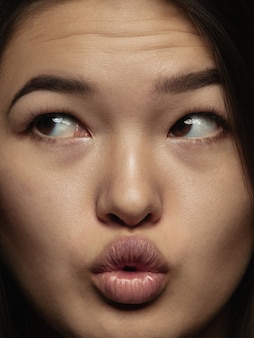若くて感情的な中国人女性の肖像画をクローズアップ。手入れの行き届いた肌と明るい表情の女性モデルの非常に詳細な写真撮影。人間の感情の概念。キスを送る。
