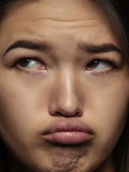 젊고 감정적 인 중국 여자의 초상화를 닫습니다. 잘 관리 된 피부와 밝은 표정으로 여성 모델의 매우 디테일 한 사진 촬영. 인간 감정의 개념. 슬프고 불쾌 해 보입니다.