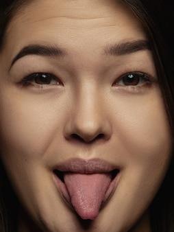 젊고 감정적 인 중국 여자의 초상화를 닫습니다. 잘 관리 된 피부와 밝은 표정으로 여성 모델의 매우 디테일 한 사진 촬영. 인간 감정의 개념. 혀를 내밀고 장난스럽게.