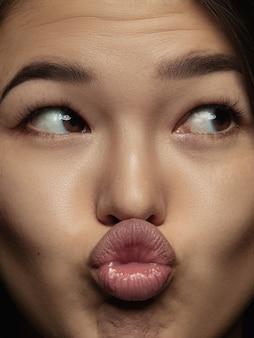 젊고 감정적 인 중국 여자의 초상화를 닫습니다. 잘 관리 된 피부와 밝은 표정으로 여성 모델의 매우 디테일 한 사진 촬영. 인간 감정의 개념. 키스 보내기.