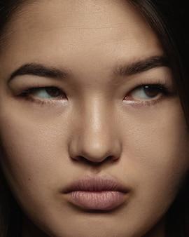 젊고 감정적 인 중국 여자의 초상화를 닫습니다. 잘 관리 된 피부와 밝은 표정으로 여성 모델의 매우 디테일 한 사진 촬영. 인간 감정의 개념. 진지하고, 측면을보고 있습니다.