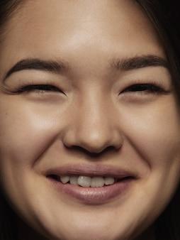 젊고 감정적 인 중국 여자의 초상화를 닫습니다. 잘 관리 된 피부와 밝은 표정으로 여성 모델의 매우 디테일 한 사진 촬영. 인간 감정의 개념. 카메라에 웃고.