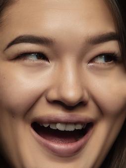 젊고 감정적 인 중국 여자의 초상화를 닫습니다. 잘 관리 된 피부와 밝은 표정으로 여성 모델의 매우 디테일 한 사진 촬영. 인간 감정의 개념. 웃고, 행복합니다.