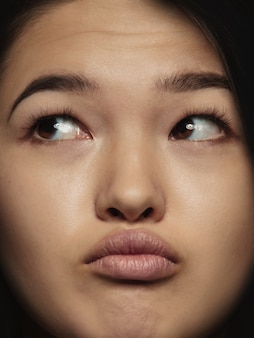 젊고 감정적 인 중국 여자의 초상화를 닫습니다. 잘 관리 된 피부와 밝은 표정으로 여성 모델의 매우 디테일 한 사진 촬영. 인간 감정의 개념. 생각하고, 측면을 봅니다.