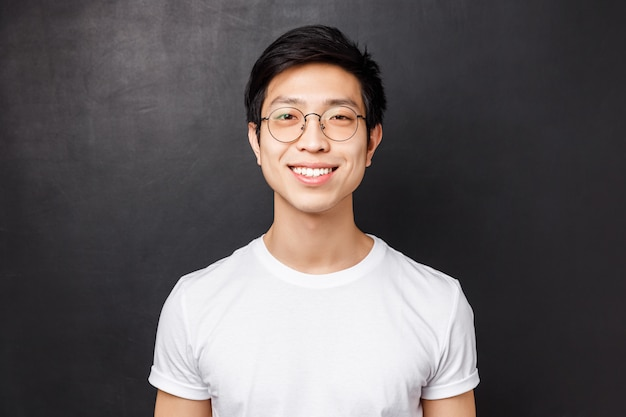 メガネとシンプルな白いtシャツの若いアジアの男のクローズアップの肖像画、カメラを見て優しい表情、晴れやかな笑顔、ブロガーがフォロワーにどのようにしてフォロワーと話しているか