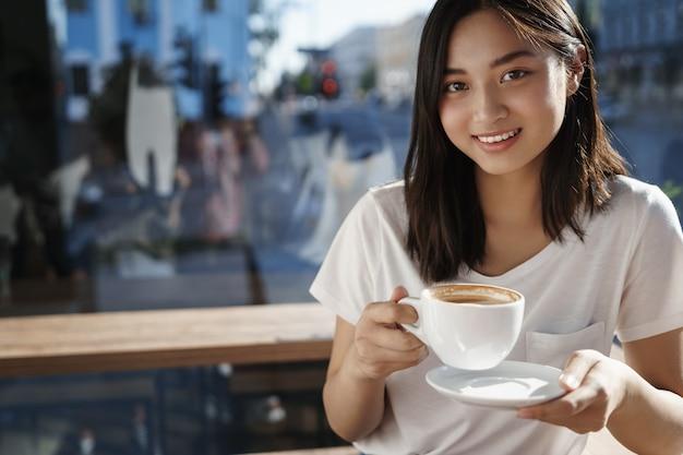 레스토랑에서 카푸치노의 젊은 아시아 여자 holdingcup의 클로즈업 초상화.