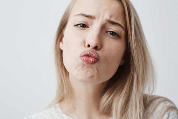 Портрет конца-вверх молодой привлекательной кавказской женщины представляя с поцелуем на ее губах с белокурыми покрашенными волосами, имеющ кокетливый взгляд чувствуя уверенно и красиво. очаровательная женская модель с удовольствием в помещении