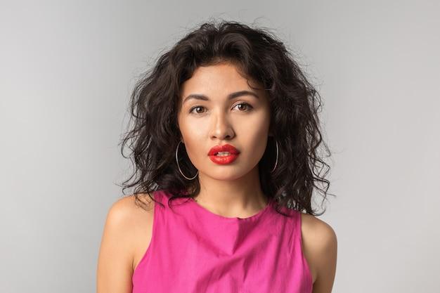 クローズアップの肖像若い魅力的なエキゾチックな日焼けした女性の巻き毛、ピンクのスタイリッシュなドレス、赤い唇、自然な表情、純粋な肌、セクシー、魅惑的な分離、夏のシーズンスタイル、ファッショントレンド