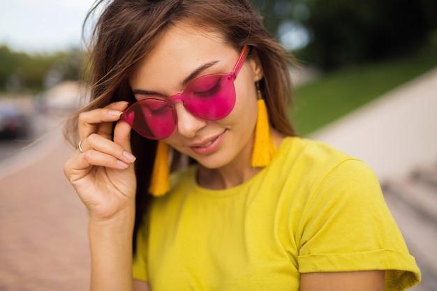 都市公園で楽しんでいる若い魅力的な笑顔の女性の肖像画をクローズアップ、ポジティブ、幸せ、黄色のトップ、イヤリング、ピンクのサングラス、夏のスタイルのファッショントレンド、スタイリッシュなアクセサリー、カラフル