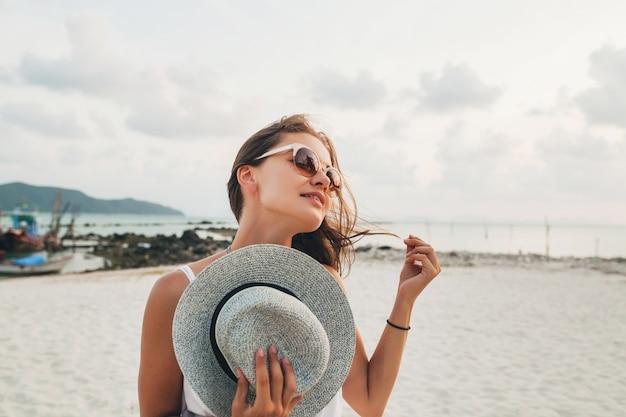 선글라스를 착용하는 열 대 해변에서 밀짚 모자를 들고 젊은 매력적인 웃는 여자의 초상화를 닫습니다