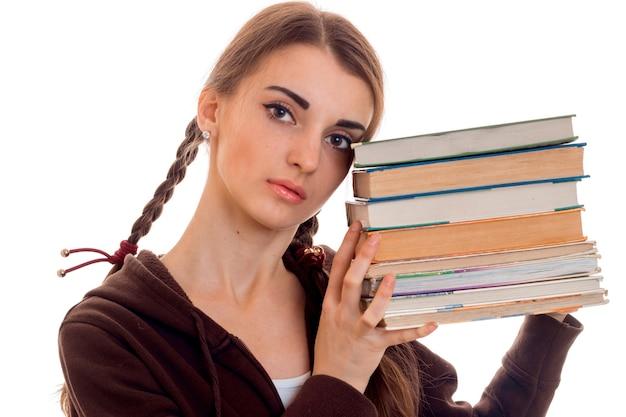白い背景で隔離の手にたくさんの本と茶色のスポーツ服を着た若い魅力的な学生の女の子の肖像画をクローズアップ