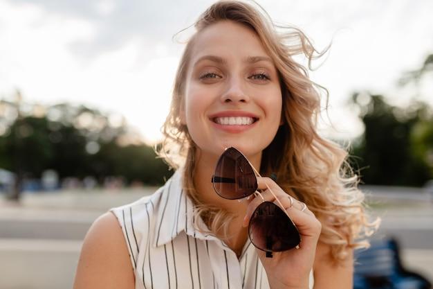 サングラスを保持している夏のファッションスタイルのドレスの街で若い魅力的なスタイリッシュなブロンドの女性のクローズアップの肖像画