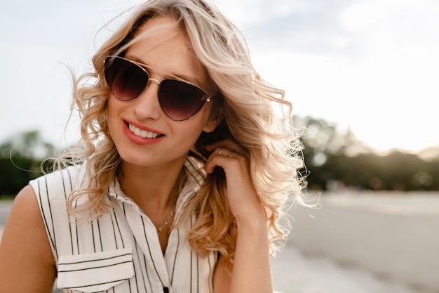 Крупным планом портрет молодой привлекательной стильной блондинки на городской улице в летнем модном платье носить солнцезащитные очки