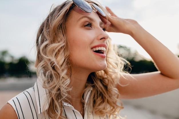サングラスをかけて夏のファッションスタイルのドレスで街の通りに若い魅力的なスタイリッシュなブロンドの女性のクローズアップの肖像画