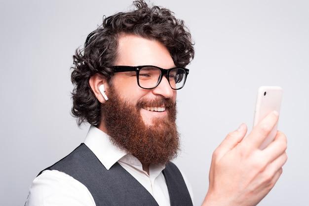 Крупным планом портрет молодого бородатого хипстера, использующего смартфон и наушники над белой стеной