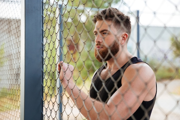 Крупным планом портрет молодого бородатого мужчины, смотрящего через металлический городской забор на открытом воздухе