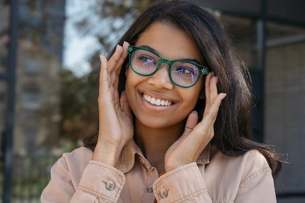 안경을 쓰고 젊은 아름 다운 아프리카 계 미국인 여자의 초상화를 닫습니다