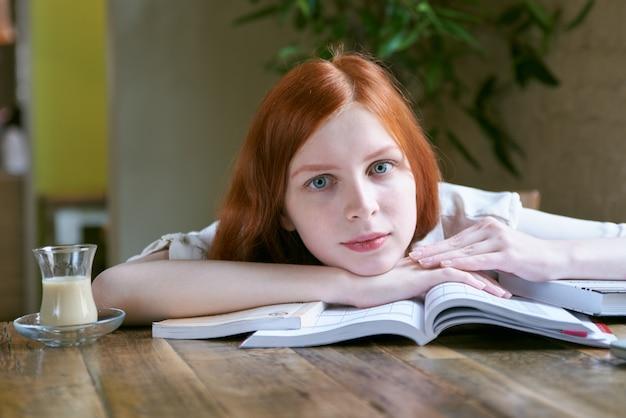 Макро портрет молодой красивой девушки студента с белой кожей и длинными рыжими волосами, сидя за столом в кафе и положив голову на книги