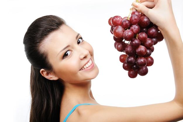 Крупным планом портрет молодой красивой счастливой женщины с гроздью винограда