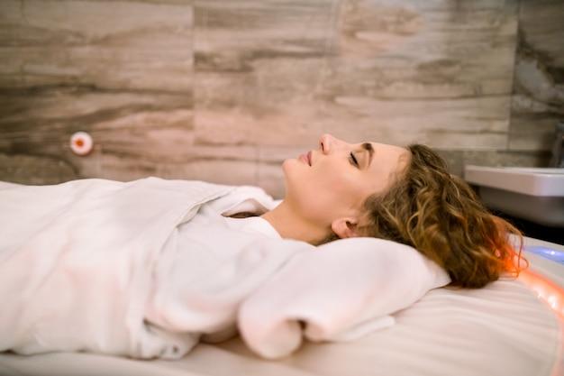 스파에서 진흙 랩 절차 동안 뜨거운 담요로 덮여 특별 뜨거운 스파 침대에 누워 젊은 아름 다운 여자의 초상화를 닫습니다.