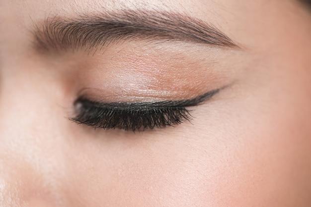 Крупным планом портрет закрытой молодой красивой женщины, зоны глаз составляют с черной стрелкой