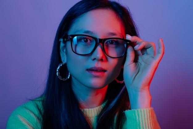 Крупным планом портрет молодой красивой женщины трогательно очки и глядя в камеру, неоновые огни