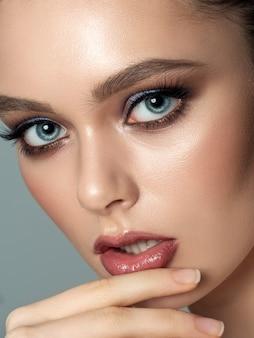 Крупным планом портрет молодой красивой женщины, касаясь ее губы