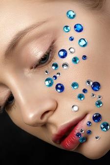 파란색 모조 다이아몬드 그녀의 얼굴을 가진 젊은 아름 다운 여자의 초상화를 닫습니다.