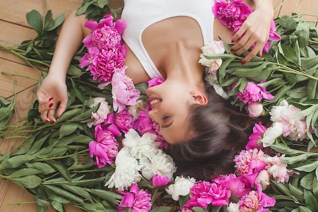 실내 꽃과 아름 다운 젊은 여자의 초상화를 닫습니다